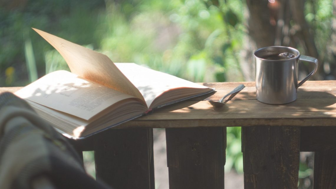 Metal mug, book, and spoon sitting on the edge of a porch railing