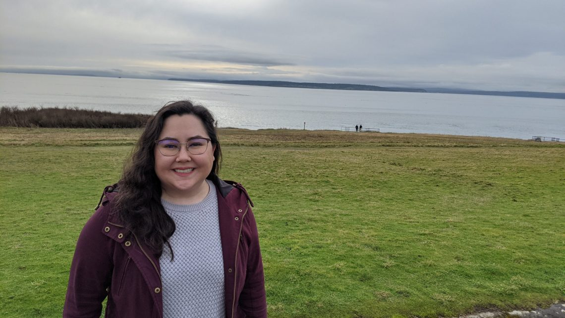 Emi Behan standing in front of a park and a lake. Emi is wearing glasses, a red jacket, and a sweater.